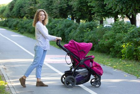 Photo pour Young mother with newborn in stroller - image libre de droit