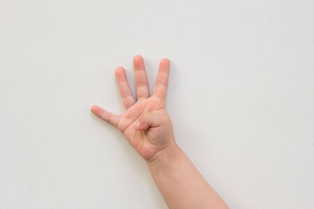 Photo pour Top view of child hand showing four fingers as number four on white background - image libre de droit