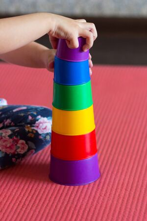 Photo pour Children hands make Pyramid using colorful stacking cups indoor - image libre de droit