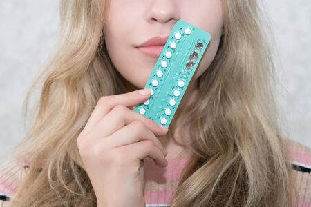 Photo pour girl holds a blister with oral contraceptives in her hand - image libre de droit