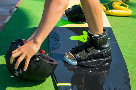 photo of a boy standing on a wakeboard on land and preparing for sports. He reached for his helmet. Safety precautions for extreme sports. Wake Park equipment. Sports, recreation, Hobbies. Summertime