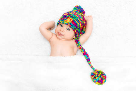 Photo pour Photo of newborn baby lying on white blanket in big bright funny knitted hat. Adoption concept, happy parenting - image libre de droit