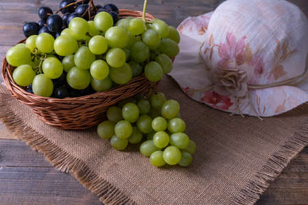 Foto für basket with grapes, on a wooden table, ripe bunches of grapes and a woman's hat - Lizenzfreies Bild