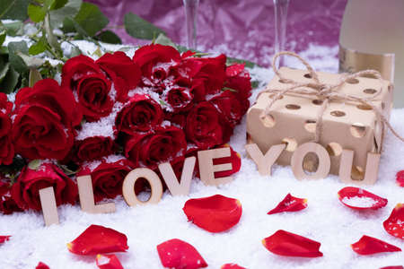 Photo pour snow, a bouquet of red roses, a bottle of champagne and the inscription I love you on a pink background - image libre de droit
