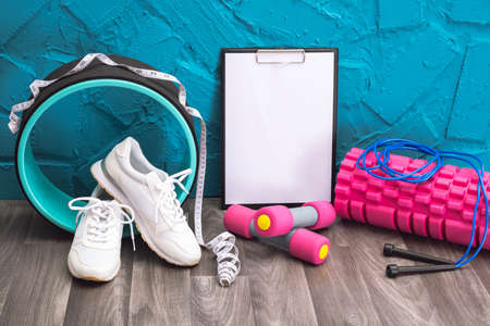 Photo pour workout at home - white sneakers, dumbbells, jump rope, measurement tape, note board and massage roller, close-up and blue background - image libre de droit