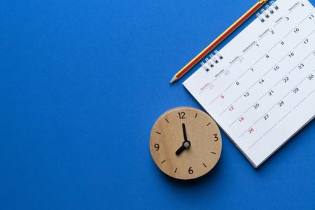 Foto de close up of calendar, clock and pencil on the blue background, planning for business meeting or travel planning concept - Imagen libre de derechos