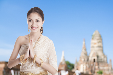 Photo for Thai woman in Thai dress costume traditional in a welcome pose, hello Sawadee with temple background - Royalty Free Image