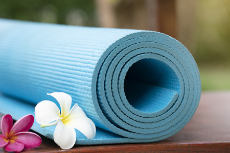 blue yoga mat and a flower outdoor, healthy and sport concept