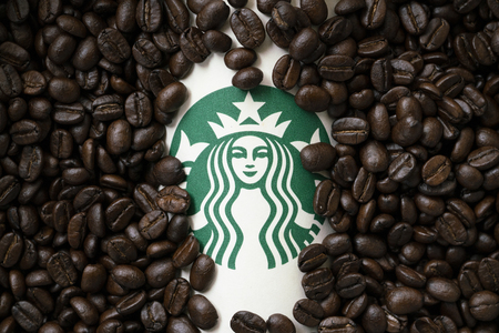 Foto de Bangkok, Thailand - Aug 26, 2018: A cup of Starbuck coffee with coffee beans background - Imagen libre de derechos