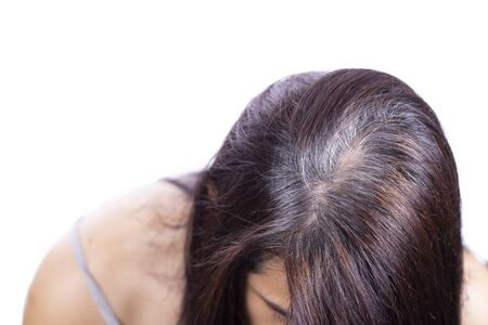 Photo pour Young woman shows her gray hair roots, isolated and white background - image libre de droit