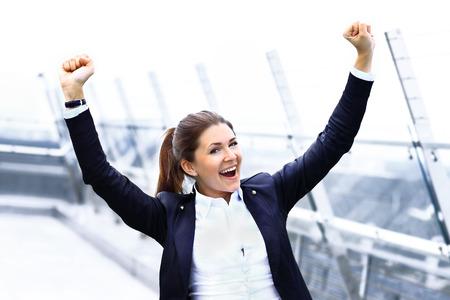 Photo pour Successful business woman with arms up celebrating - image libre de droit