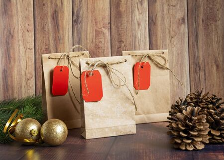 Photo pour Vintage handmade gift boxes made of kraft paper on a wooden background in the Christmas style, decorated with golden Christmas balls, cones, fir branch. Christmas, New Year, winter holiday. Kraft package, holiday concept, top view, flat lay. Mocap. - image libre de droit