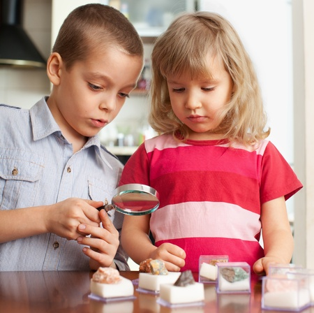 Children are playing with a magnifying glass, looking at collection of stones