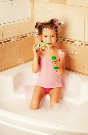Glamour girl blow bubbles in the bathtub. Child in bathroom