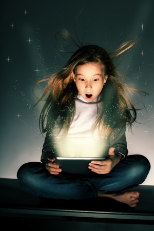 Surprised girl looking at a magic tablet. Child with tablet computer