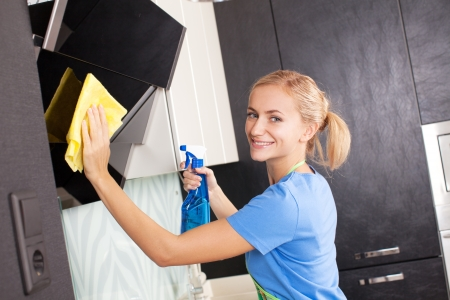 Woman cleaning kitchen. Young woman washing kitchen hood