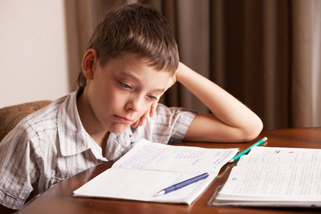 Sad boy doing homework. Child education
