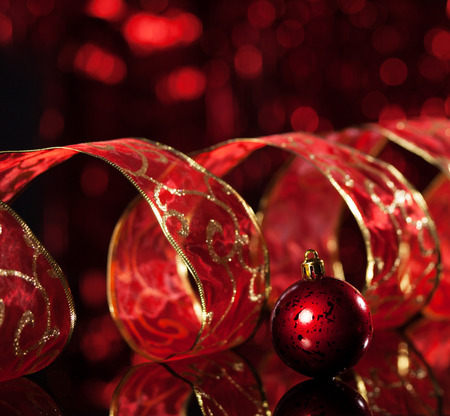 Red christmas sphere with ribbon on black background. Christmas decoration. Celebration