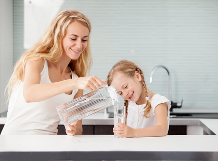 Photo for Child with mother drinking water from glass. Happy family at home in kitchen - Royalty Free Image