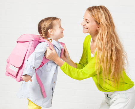 Foto de Mother helps her daughter get ready for school. Mom support child to wear a backpack - Imagen libre de derechos