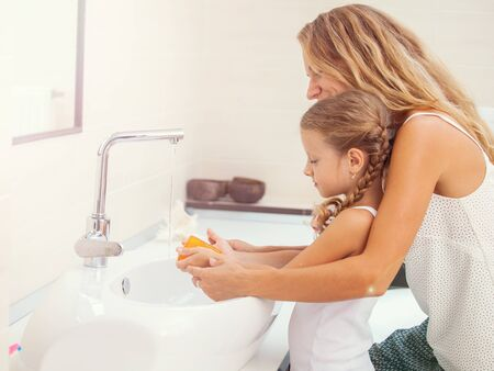 Photo pour Mother and daughter washing their hands - image libre de droit