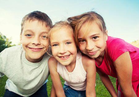 Photo pour Happy children at summer. Girl and boy outdoors - image libre de droit