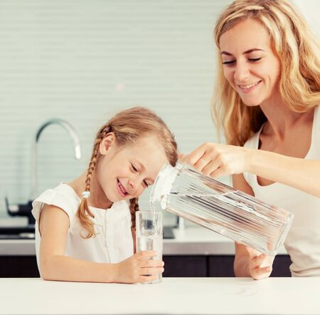 Photo pour Child with mother drinking water from glass. Happy family at home in kitchen - image libre de droit
