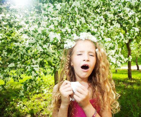Photo pour Sneezing girl near blowing tree. Child with a handkerchief. Allergy - image libre de droit