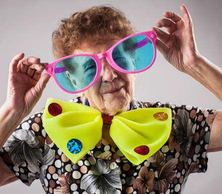 Photo pour Merry old woman. Happy fun granny. Adult funny female on party - image libre de droit
