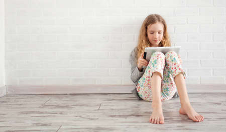 Photo pour Child with tablet. Girl playing tablet at home - image libre de droit