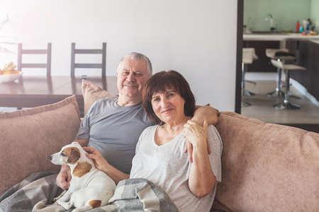 Photo pour Happy elderly couple sitting on sofa at home. Seniors with dog - image libre de droit