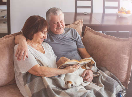 Photo pour Happy elderly couple sitting on sofa and reading book at home. Seniors with dog - image libre de droit