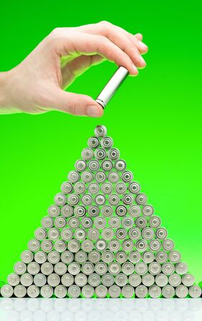 Ecology recycling concept, nature energy, man hold in hand used or new battery piramide, rechargeable AA accumulator, alkaline batteries in row on green background