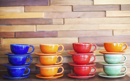 Colorful coffee cups on brick wall background