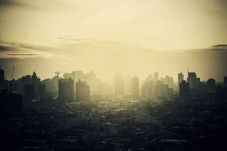 Hazy skyline of Bangkok City at dawn, smoke with sunrise.