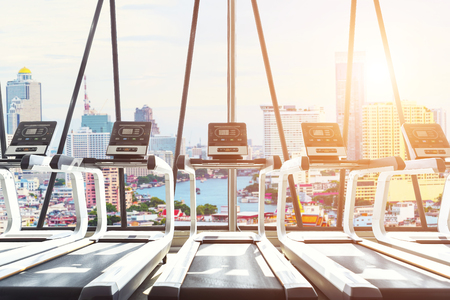 Interior of modern treadmills in gym at sunrise with view of city outside. Fitness background concept.