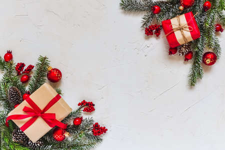 Foto de Christmas light background. Corner decorated with fir twigs and Christmas baubles. Red berries, candies, gifts, snowflake and fir cone. Top flat view with text copy-space. - Imagen libre de derechos