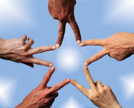 Five hands with different skin-color, their fingers building a star