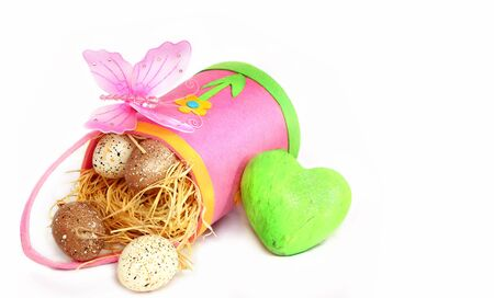 Four easter eggs in a pink bag with a green heart and pink butterfly, isolated on white background