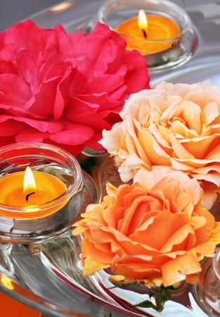 Dish of glass and water with swimming roses and candles for aromatherapy, reiki, ayurveda
