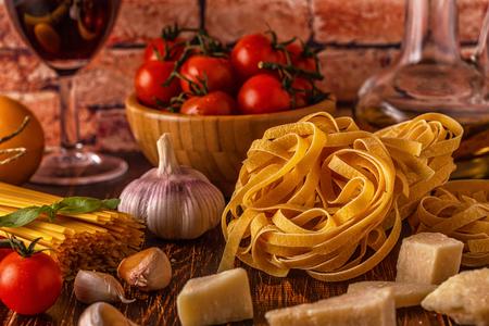 Foto de Products for cooking - pasta, tomatoes, garlic, olive oil and red wine. Selective focus. - Imagen libre de derechos