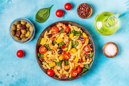 Foto de Fusili pasta salad with shrimps, tomatoes, peppers, spinach, olives, top view. - Imagen libre de derechos