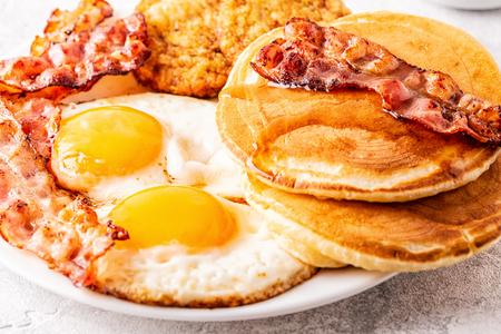 Photo pour Healthy Full American Breakfast with Eggs Bacon Pancakes and Latkes, selective focus. - image libre de droit