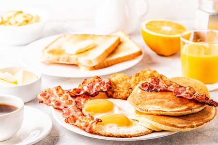 Foto de Healthy Full American Breakfast with Eggs Bacon Pancakes and Latkes, selective focus. - Imagen libre de derechos