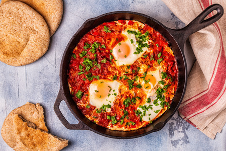 Photo pour Shakshuka in a Frying Pan. Eggs Poached in Spicy Tomato Pepper Sauce. - image libre de droit