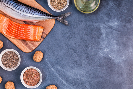 Foto de Sources of omega 3 - mackerel, salmon, flax seeds, hemp seeds, chia, walnuts, flaxseed oil. Healthy eating concept. Top view with copy space. - Imagen libre de derechos