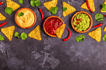 Foto de Mexican food background: guacamole, salsa, cheesy sauces with ingredients on black background, top view. - Imagen libre de derechos
