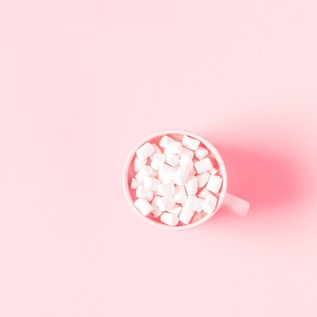 Photo pour Cup of hot chocolate and marshmallows on a pink pastel background. Flat lay, top view. - image libre de droit