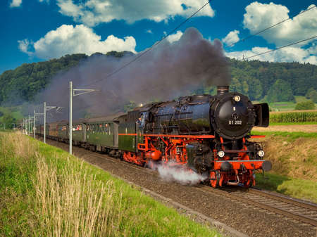 Photo pour A German steam locomotive with passenger cars traveling through the Swiss countryside. - image libre de droit