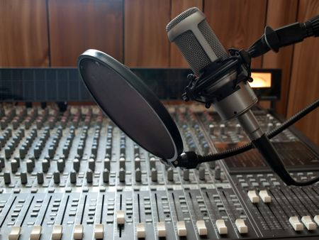 a studio vocal microphone over a mixing board console